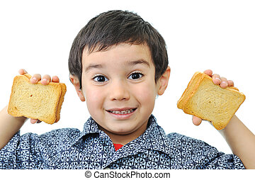 Little boy showing satisfaction while making a peanut butter sandwich