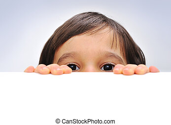 Child holding an empty sign over a white background, hiding behind