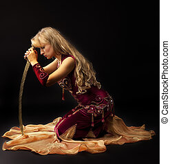 Sadness woman in arabian costume sit with saber