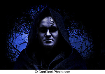 Man in hood on the spooky forest background