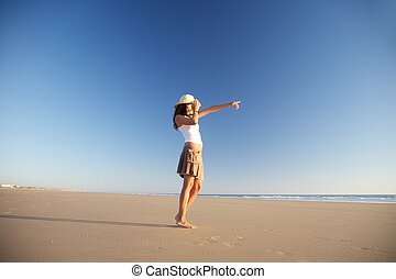 pointing woman with hat at beach
