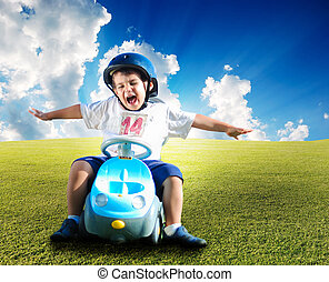Happy kid on green meadow driving a car