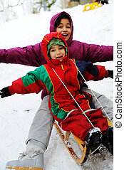 children have fun together sliding downhill on a pleasant...