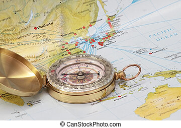 Modern brass compass over old Asian map background