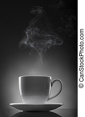 white cup with hot liquid and steam on black