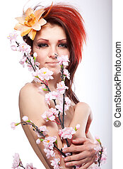 Portrait of beautiful naked woman with spring flower in hair on white