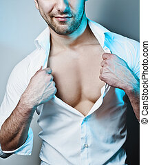 Sexy Male Model Unbuttoning His White Shirt - Studio shot of...