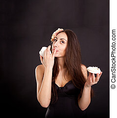 Pretty young girl eating cake on dark background