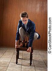 Man Stands On Chair - Young Caucasian man stands on a chair,...