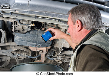 Changing oil filter - Experienced car mechanic changing oil...