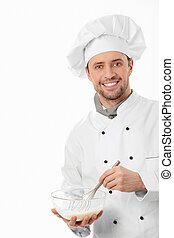 Confectioner - A young cook mixes on a white background
