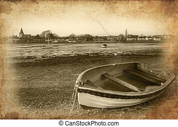 Rowing boat in foreground on low tide harbour at sunset with...