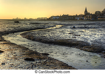 Harbour at low tide at sunset with local town in distance landscape