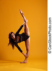 Side splits dance pose on yellow - Beautiful young female...