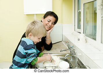 Mother watching child do the dishes in the family kitchen