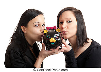 two young women piggy bank kissing - closeup of two young...