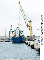 ship on harbor with crane under cloudy sky