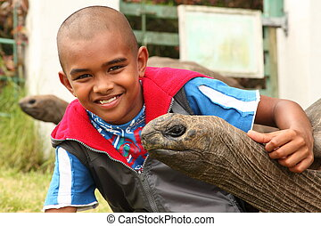 Smiling boy with giant tortoise - School boy visits the...