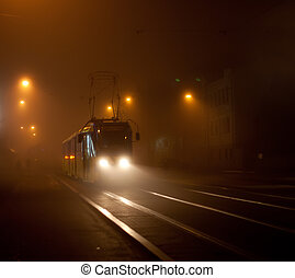 Tram moving on city street in the fog at night