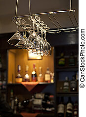 Wine glasses hanging near bar counter with wine bottles on...