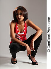 Beautiful girl crouching in studio - Portrait of beautiful...