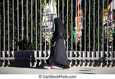 The Muslim woman going along the street.