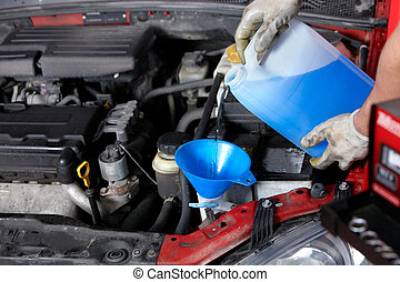Auto mechanic - Windscreen washer. Mechanic working in auto...