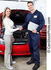 Auto repair - Handsome mechanic and client woman in auto...