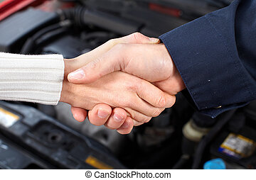Auto repair - Handshake. Mechanic and client woman in auto...