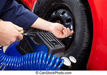Tire pressure - Mechanic inspecting the tire pressure in...