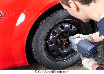 Auto repair - Mechanic changing wheel on car with impact...
