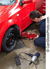 Auto repair - Handsome mechanic changing a tire. Auto...