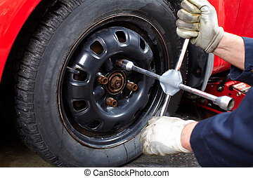 Auto repair - Mechanic changing wheel on car with a wrench.