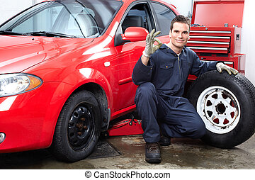 Auto repair - Handsome mechanic changing wheels in auto shop...