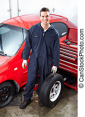 Auto repair - Handsome mechanic changing wheels in auto...