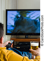 Watching television - Guy enjoying his evening watching...