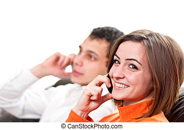 Happy couple talking on cell phones. Isolated on white
