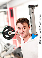 Man lifting weights in fitness club - barbell