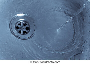Running water drains down a stainless steel sink
