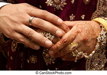 Asian wedding couple holding hands - Henna and jewelery