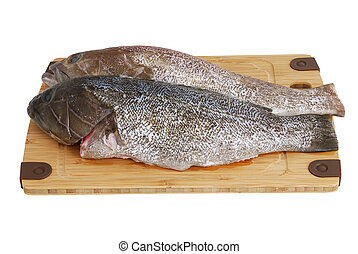Two scaled grouper fish on bamboo cutting board - Ready for...