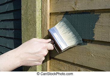 painting the fence - painting wood stain onto a fence with a...