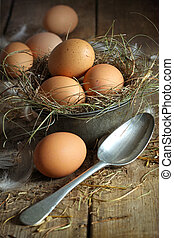 Fresh brown eggs in old tin container with spoon on wood...