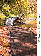 Autumn landscape with stairs, bridge and pond
