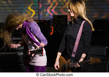 Woman on rock concert - Young women playing on guitars in...