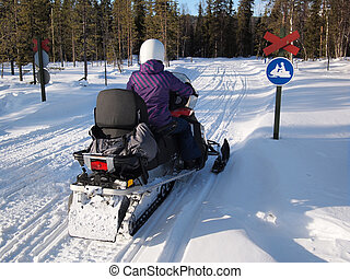 Person on a snow scooter - Person on a snow mobile on a...