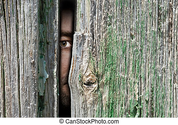 Under cover - Male person hide behind a wooden wall