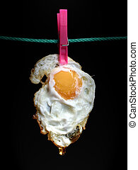 Hanging fried egg with last oil drop