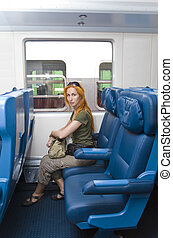 Interior of a passenger train with young woman, sitting into...