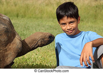 Young boy with giant tortoise